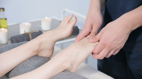 Close-up of a male physiotherapist doing foot massage to a young girl in a beauty and health spa. Foot and body care concept