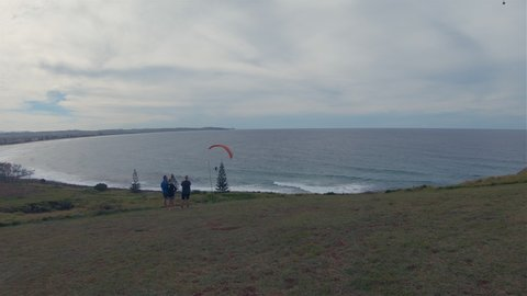 Paragliders Paragliding. People Watching Para Gliders Gliding High In Windy Cloudy Sky At Pat Morton Lookout Headland Sea Coastline Hills.Outdoor Leisure Activity.Lennox Head Landscape Australia