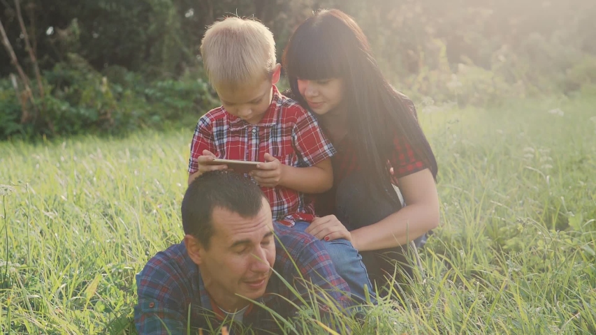 Happy family teamwork lifestyle outdoors have fun concept outdoors slow motion video . mom a dad and son take photo with smartphone in nature are sitting on the grass have fun playing .mom girl dad   Shutterstock HD Video #1037217992