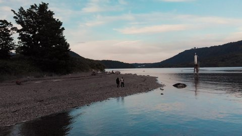 A happy in love couple holding hands walking on a beach at sunset near a beautiful inlet near Deep Cove, North Vancouver - 4K 24FPS