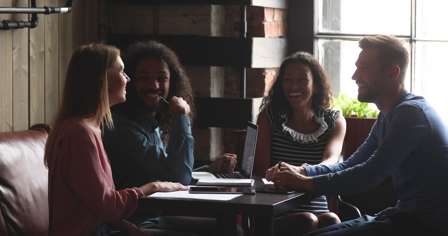 Happy multiracial diverse students or coworkers team study work together share cafe table talking laughing at funny joke having fun enjoy communication at group meeting in coffee shop room interior | Shutterstock HD Video #1037298182
