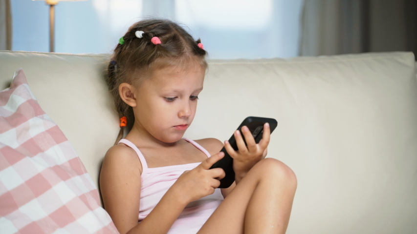 Little Girl Child Home On Sofa Playing On Smartphone   Shutterstock HD Video #1037314502