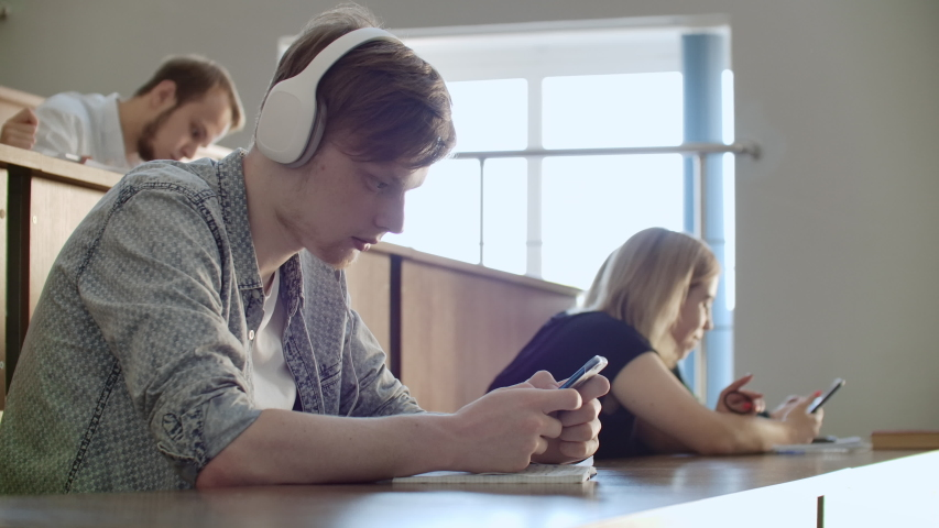 A student sitting in a university auditorium with a large group of people sits in headphones and listens to music and looks at the smartphone screen. It is in a state of calm. Class break.   Shutterstock HD Video #1037361212