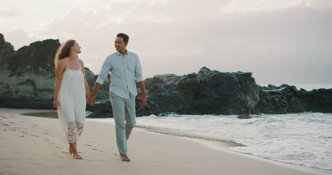 Happy mixed race couple walking together holding hands on the beach at sunset