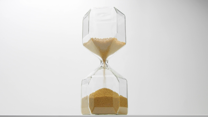 Closeup of a glass sand clock on white with golden balls instead of sand falling on white | Shutterstock HD Video #1037505752