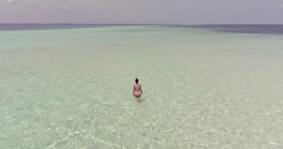 Aerial view of a woman swimming in the Maldive sea in a sandbank | Shutterstock HD Video #1037507222