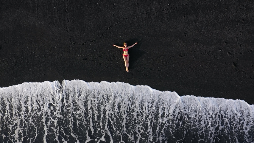 Top view of a girl in a red swimsuit lying on a black beach on the surf line. Coast of the island of Tenerife, Canary Islands, Spain.