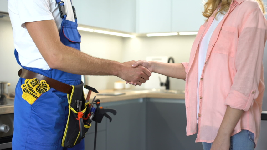 Plumber with tools shaking client hand, technical maintenance, repair services | Shutterstock HD Video #1037661782