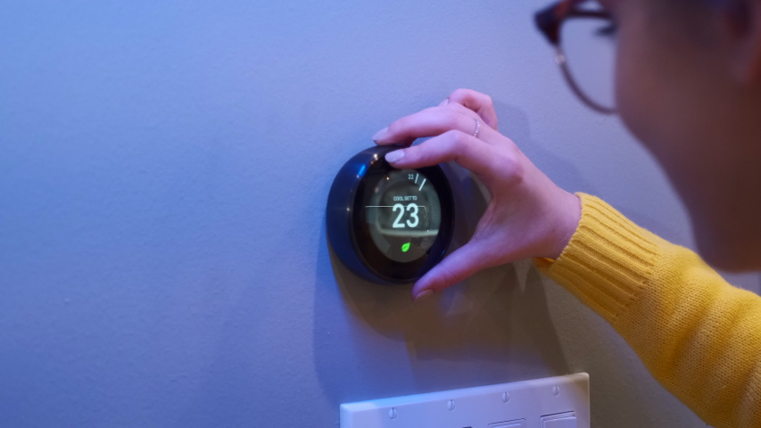 Woman Adjusting Smart Thermostat Gadget At Home | Shutterstock HD Video #1037891492