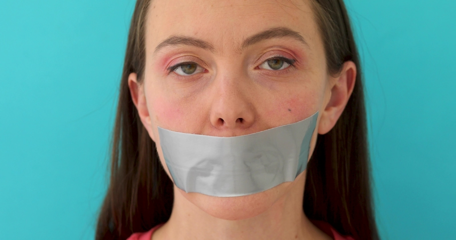 Femail mouth taped. Woman wants to speak but it isnt allowed on blue background #1038075932