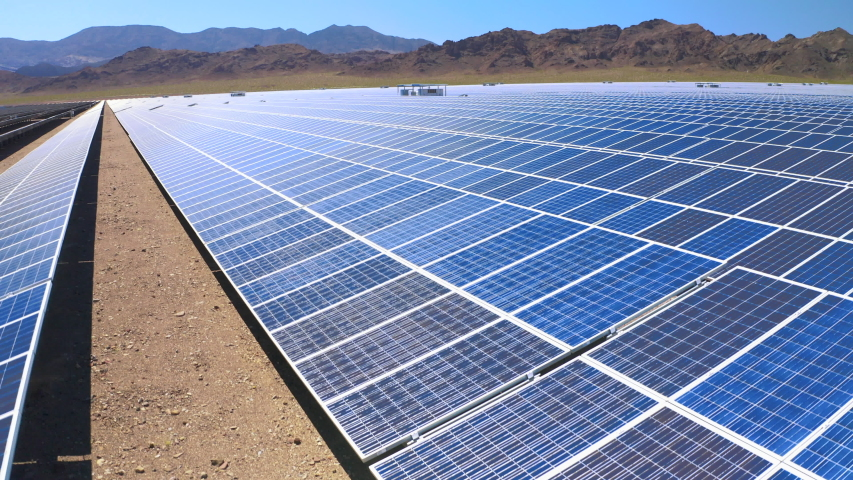 Drone rises up over the solar cells forming long blue rows on the ground of solar farm in Nevada,USA. The view of the vast farm territory opens from the height. Mountain range at the backfront is seen   Shutterstock HD Video #1038078662