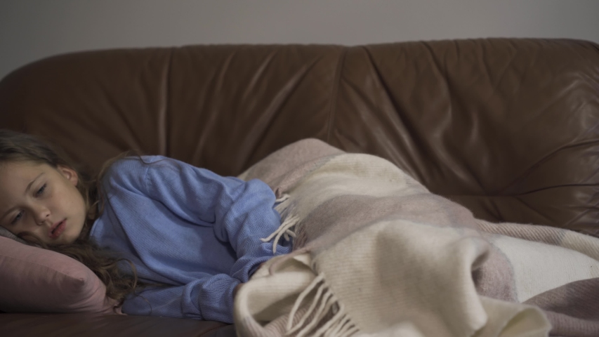 Sick young caucasian girl coughing while lying under blanket at home. The child has fever. Concept of health, illness, sickness, common cold, treatment | Shutterstock HD Video #1038103052