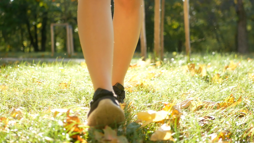 Female steps along the colorful autumn foliage of the city park. Close up legs and shoes view #1038428492
