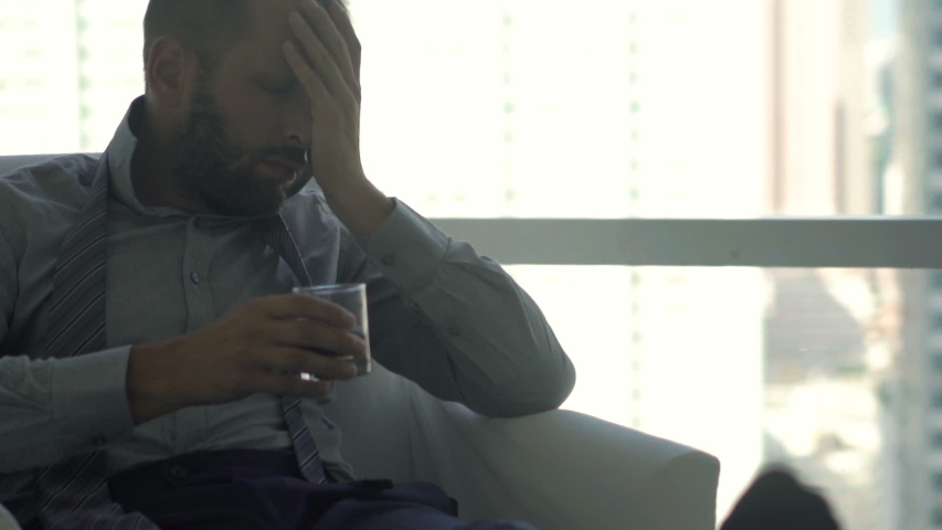 Drunk businessman drinking alcohol sitting on chair at luxury home | Shutterstock HD Video #1038457982