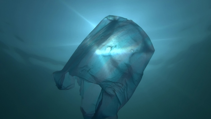 Plastic pollution,  used blue plastic bag slowly drifting underwater in the sun lights. Low-angle shot, Backlighting. Plastic debris underwater. Plastic garbage environmental pollution problem | Shutterstock HD Video #1038458462