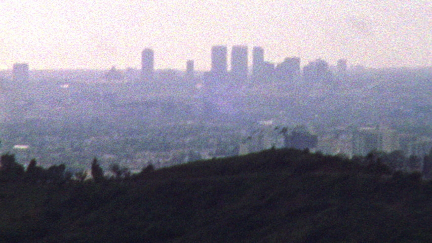 Shaky old looking archival footage of Los Angeles skyline and hills in the distance | Shutterstock HD Video #1038494222
