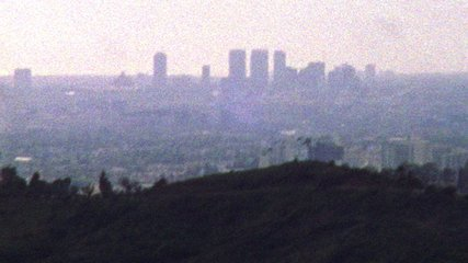 Shaky old looking archival footage of Los Angeles skyline and hills in the distance