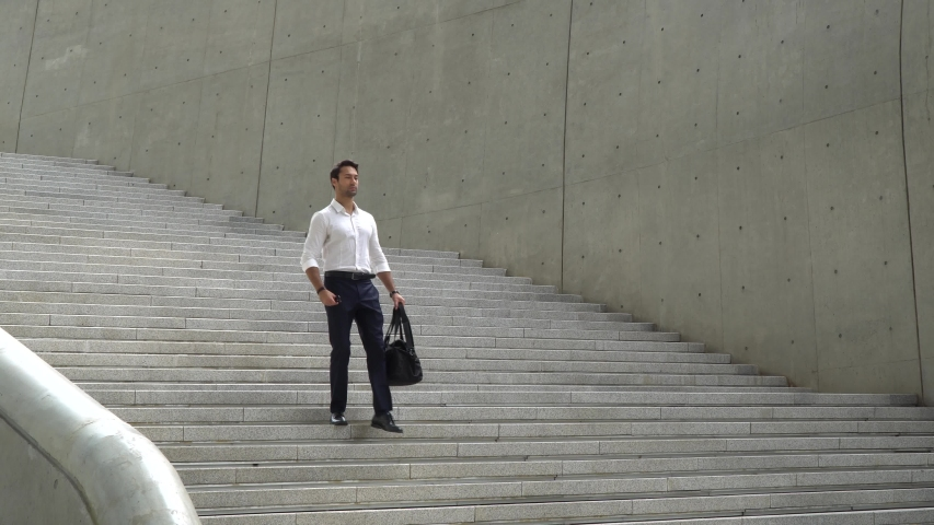 Mid shot of handsome and fit European man with dark hair in white collared shirt and dark trousers is walking down a grand modern concrete staircase towards camera and out of frame #1038785552