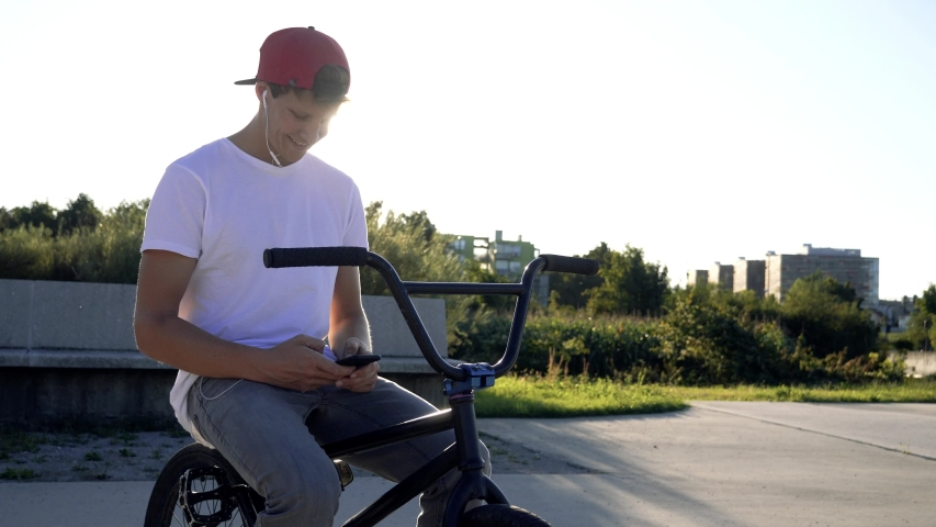 SLOW MOTION Portrait of happy handsome bmx rider, using mobile phone while riding a BMX bike, smiling, messaging friends via social networks. People, lifestyle and communication concept   Shutterstock HD Video #1038864692