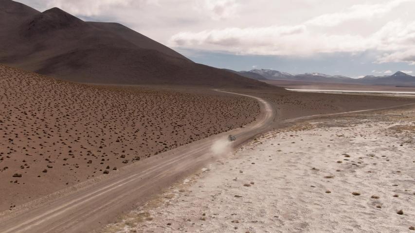 Driving down DRONE shot of car in desert on Bolivia's Salt Flats. DRONE Shot of couple in Salar de Uyuni salt flat. Dry landscape, empty. Holiday, vacation, driving, roadtrip, journey, long road
