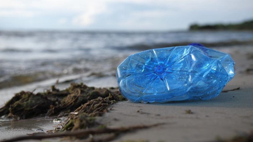 Close-up. Near the sea lies a plastic bottle. Environmental pollution by plastic.   Shutterstock HD Video #1038911222