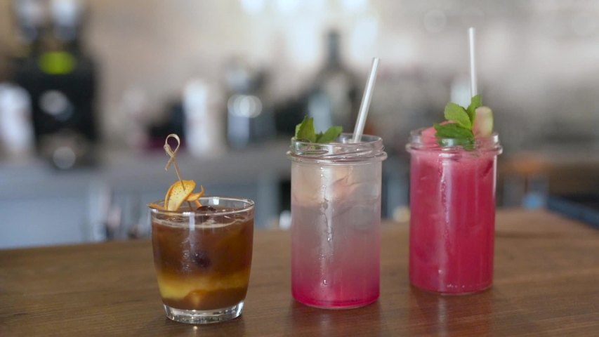 Handheld sliding shot of three alcoholic beverage cocktails on a bar counter top | Shutterstock HD Video #1038948962