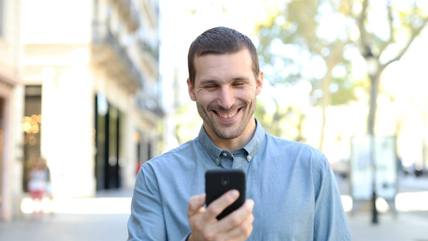 Front view portrait of a happy adult man walking towards camera using smart phone in the street | Shutterstock HD Video #1039011722