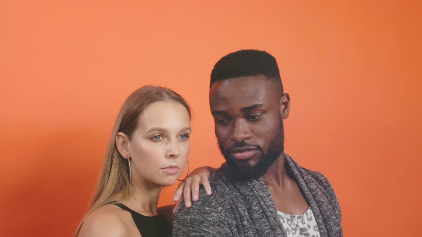 Sexy multiracial man and woman doing a fashion photo shoot in a professional studio | Shutterstock HD Video #1039178762