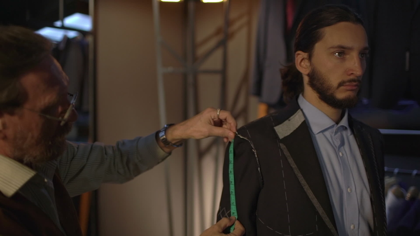Serious-looking bearded businessman standing still while tailor taking measures with measuring tape, adjust sleeves and jacket pieces, create handmade personal suit at atelier. Fashion concept | Shutterstock HD Video #1039192322
