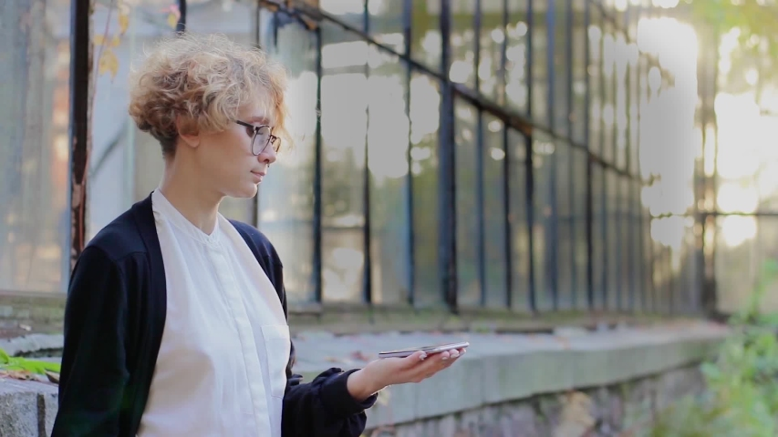 Curly young woman in glasses interacts with a hud hologram with text CRM system. Blonde girl in white and black clothes uses technology of the future mobile screen | Shutterstock HD Video #1039205252