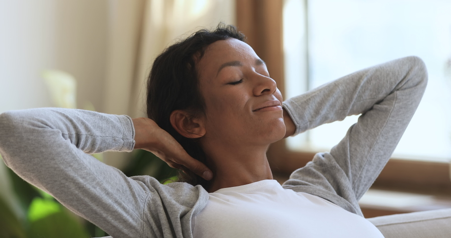 Relaxed happy healthy young african woman resting in cozy home enjoying stress free weekend looking dreaming breathing fresh air lounge on comfortable sofa hands behind head, peace of mind concept | Shutterstock HD Video #1039317692