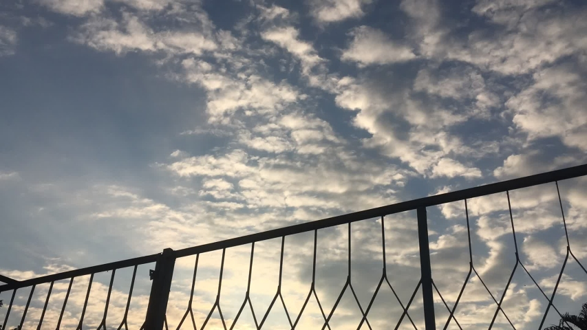 Time lapse sky clouds mesh fence sunset | Shutterstock HD Video #1039323722