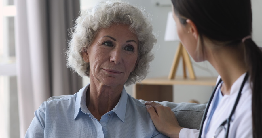 Senior old woman talking to young female nurse doctor help patient at checkup medical consultation at home hospital, elderly grandma listen caregiver giving support, older people healthcare concept | Shutterstock HD Video #1039338032