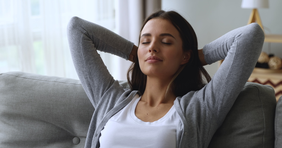 Serene attractive young woman resting on couch taking deep breath of fresh air holding hands behind head, healthy calm lady relaxing on comfortable sofa napping feel stress free at home lounge alone | Shutterstock HD Video #1039338122
