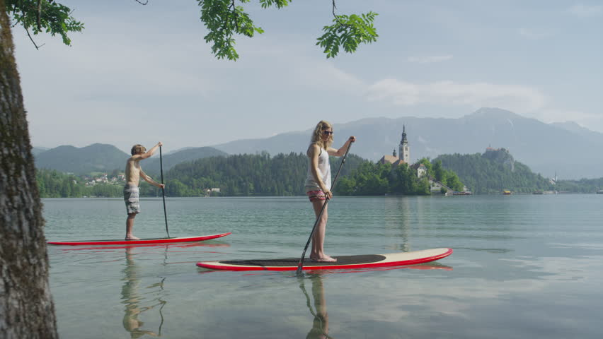 SLOW MOTION: Young couple on a date stand up paddling on lake Bled on beautiful sunny day | Shutterstock HD Video #10394342