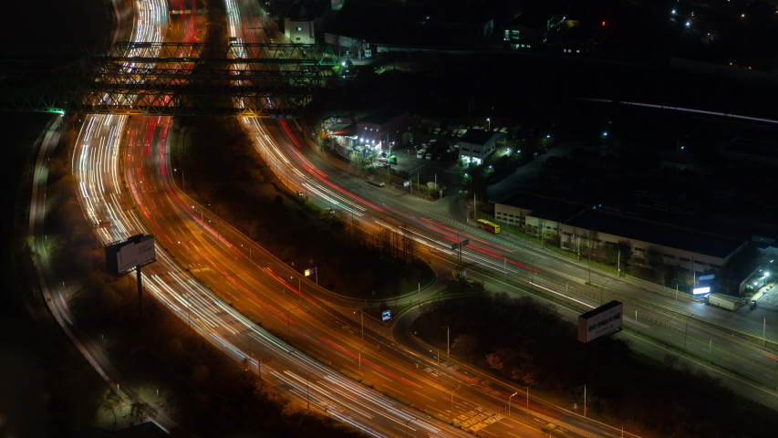 Timelapse heavy traffic on modern Seoul multi-lane parallel highways surrounded by trees and small buildings with bright illumination at deep night zoom in #1039515812