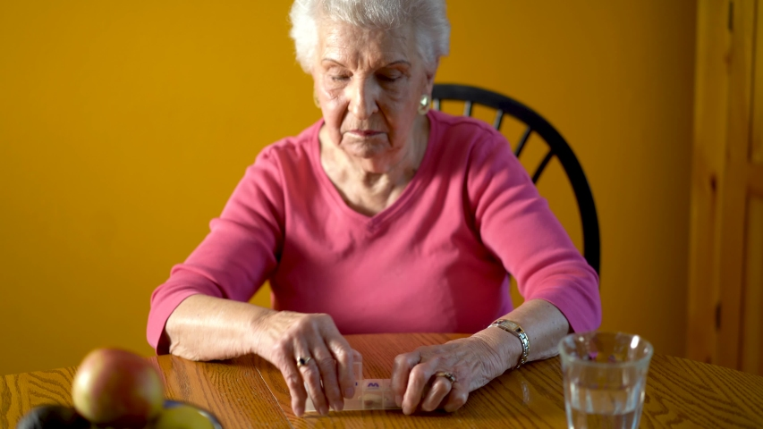 Front shot of elderly woman opening pill organizer and taking pills for Thursday.