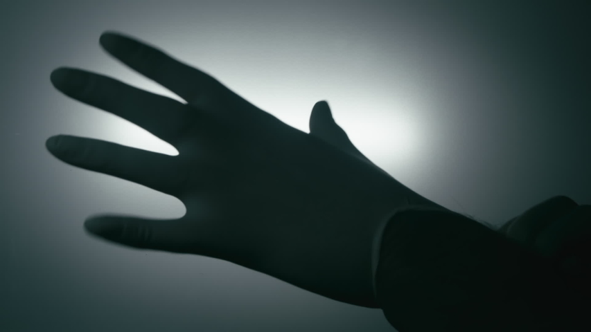 Silhouette of hand putting on latex medical glove, isolated against background, close up. | Shutterstock HD Video #1039852292
