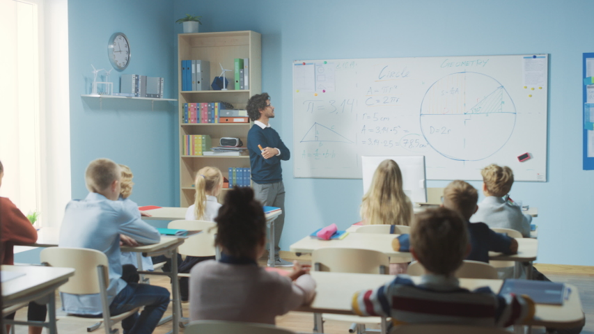 Talented Teacher Explains Lesson to a Classroom Full of Bright Diverse Children. In Elementary School with Group of Smart Multiethnic Learning Geometry and Physics, Boy Raising Hand with an Answer | Shutterstock HD Video #1039966982