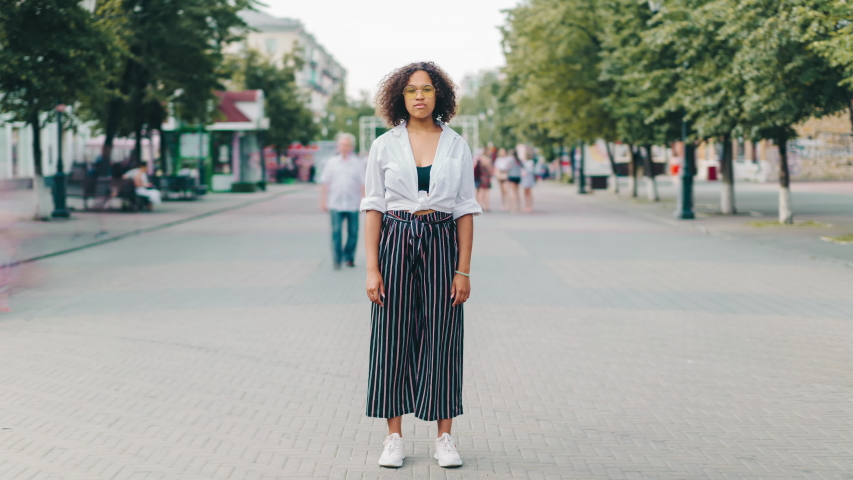 Time lapse portrait of attractive African American girl standing outdoors on pedestrian street and looking at camera with serious face. People and lifestyle concept.