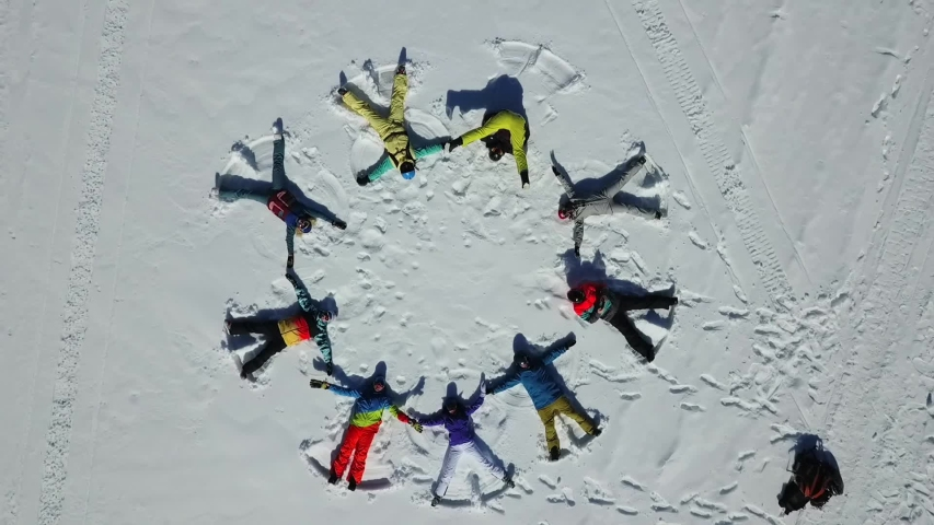Aerial top view on skiers making angels in the snow and lazing in the shape of a circle. People in colourful sport clothes. Andorra.