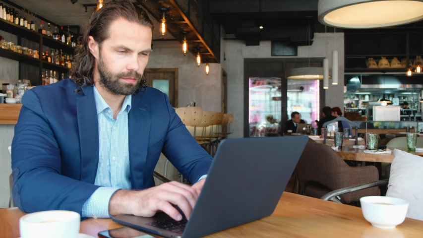 Distant view of a young businessman sitting at a table in a cafe using the phone. Successful people, daily routine. Entertaining, relaxing, chatting. | Shutterstock HD Video #1040145962