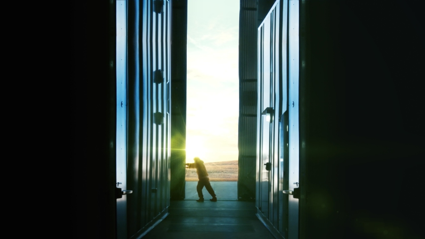 Man Opening Door of a Container Warehouse or Hangar at Sunset. 4K resolution. | Shutterstock HD Video #1040351132