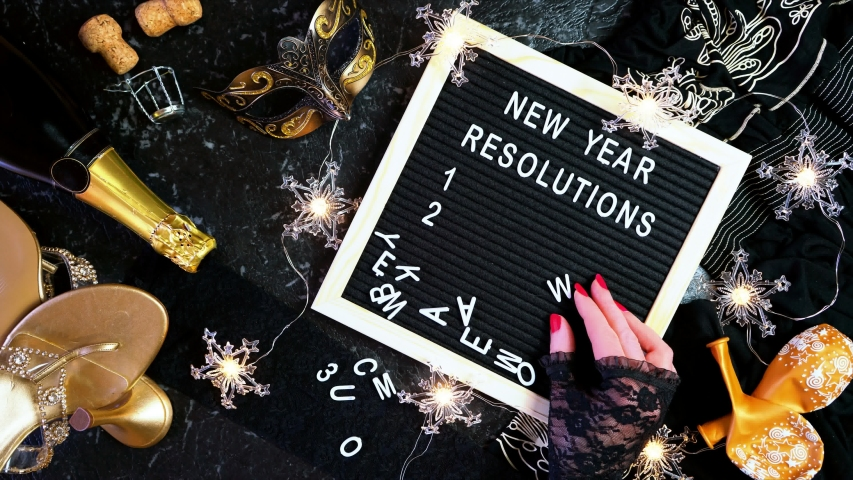 New Year's Eve resolutions flatlay with letter board and black and gold party decorations stop motion animation continuous loop. | Shutterstock HD Video #1040368502