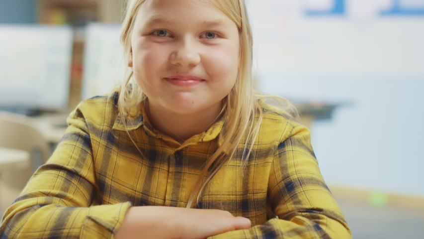 Portrait of a Cute Little Girl with Blond Hair Sitting at her School Desk, Smiles Happily. Smart Little Girl with Charming Smile Sitting in the Classroom. Close-up Camera Shot | Shutterstock HD Video #1040462732