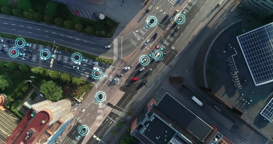 Top down aerial drone. Autonomous self driving cars moving through city. Traffic lights and rush hour. Artificial intelligence in automotive industry. Sunny day at Helsinki Finland.