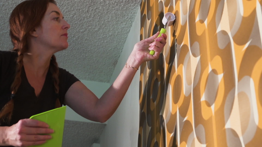 Real woman improving, renovating and decorating her home by hanging 1970's retro wallpaper | Shutterstock HD Video #1040883182
