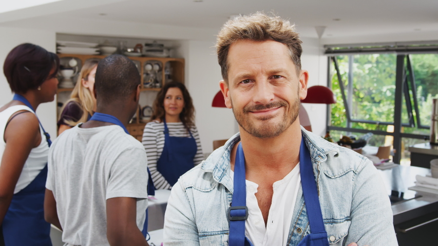Portrait Of Smiling Mature Man Wearing Apron Taking Part In Cookery Class In Kitchen | Shutterstock HD Video #1040910392