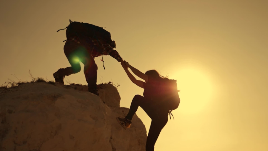 Happy family. Team work in business and life. A man holds out a helping hand to a girl while climbing to a height. The path to success and victory. Team Success Concept | Shutterstock HD Video #1040998052
