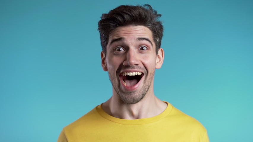 Amazed european man shocked, saying WOW. Handsome guy with stylish hairdo surprised to camera over blue background. | Shutterstock HD Video #1041091162